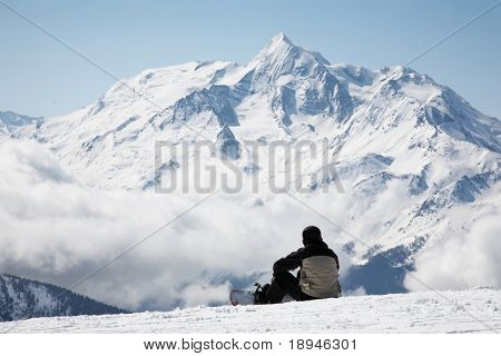 Snowboarder takes a break; in background the french alps, Europe.