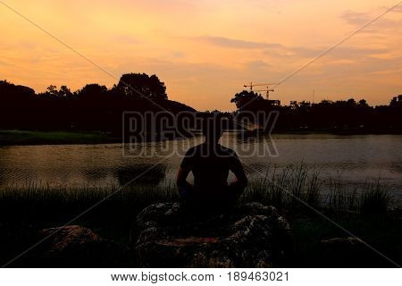 Silhouette of man meditating and yoga practicing at sunset