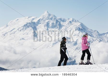 A couple of skiers take a break; in background the french alps, Europe.