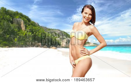 people, summer holidays, vacation and travel concept - happy smiling young woman posing in bikini swimsuit posing over exotic tropical beach and sea shore background