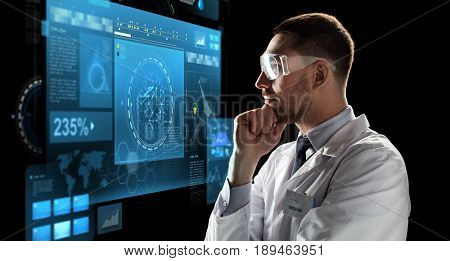 technology, science, and people concept - male doctor or scientist in white coat and safety glasses looking at virtual screen over black background