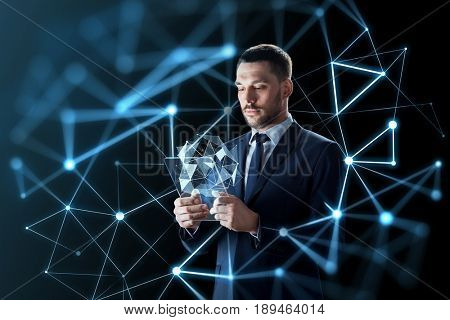 business, augmented reality and future technology concept - businessman in suit working with transparent tablet pc computer and virtual low poly shape projection over black background