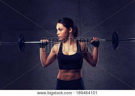 sport, fitness, bodybuilding, weightlifting and people concept - young woman with barbell flexing muscles in gym