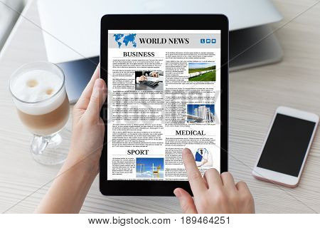 woman hands holding tablet computer with app world news screen over table notebook and phone