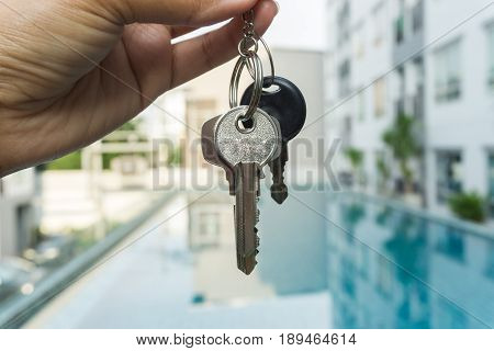 A Hand Is Holding A Key From The New Condominium High Rise Condominium Buildings And Swimming Pool B
