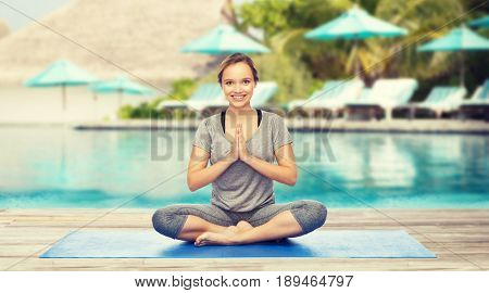 fitness, sport, people and healthy lifestyle concept - woman making yoga meditation in lotus pose on mat over beach and swimming pool background