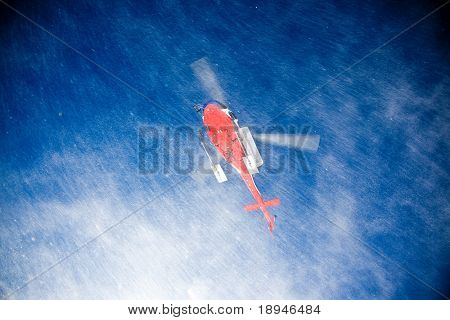 Heli Skiing Helicopter is landing on a ski slope.