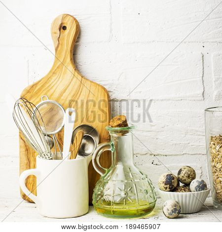 Kitchen tools, olive cutting board on a kitchen shelf against a white brick wall. selective