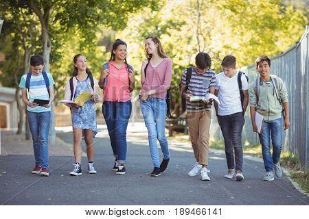 Smiling school kids walking on road in campus at school