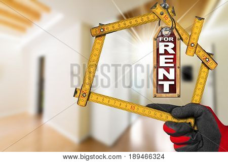 Apartment For Rent - Hand with work glove holding a wooden meter ruler in the shape of house. Interior of a blurred house