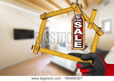 Apartment For Sale - Hand with work glove holding a wooden meter ruler in the shape of house. Interior of a blurred house
