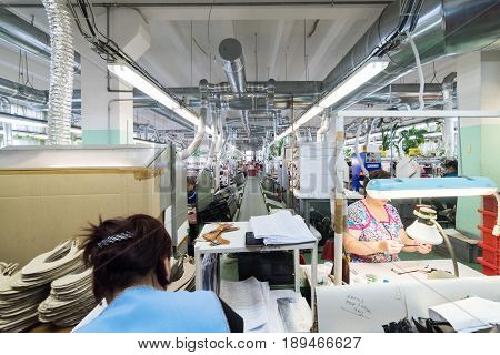 MOSCOW, RUSSIA - FEBRUARY 21, 2017: Moscow shoe factory JSC RALF RINGER . Female and male workers on a sewing machine.