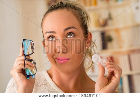 Young blonde woman holding contact lens case on hand and holding in her other hand a blue glasses on blurred background., eyesight and eyecare concept.
