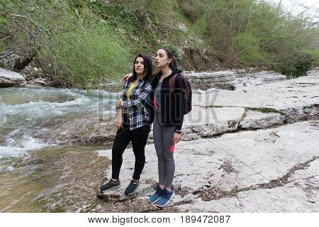 Young travelers standing together by the creek and looking away at a view. Travel adventure and hiking activity active and healthy lifestyle on summer vacation and weekend tour