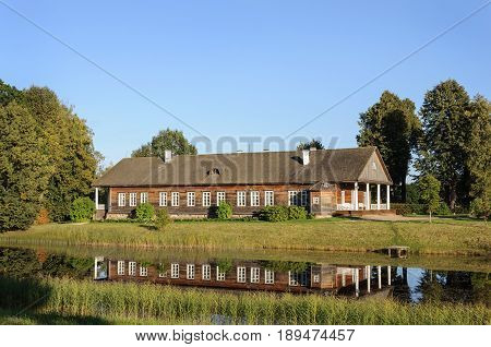 Manor house and pond in Trigorskoe village on sunset. State Museum-reserve of A. S. Pushkin Pskov Region Russia.