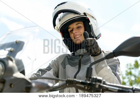 pretty girl sits on a motorcycle and has a helmet on her head