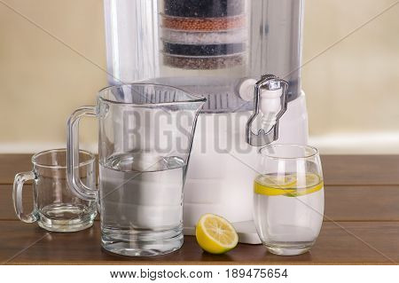 Filter system of water purifier with two glasses of water one filled until middle with a lemon inside and an empty pitcher on wooden table.