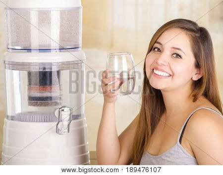 Beautiful smiling woman holding a glass of water, with a filter system of water purifier on a kitchen background.