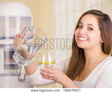 Beautiful smiling woman holding a glass of water in one hand and a pitcher of water in her other hand, with a filter system of water purifier on a kitchen background.