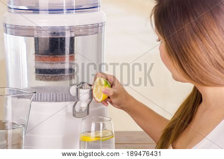 Beautiful woman holding a cut lemon in her hand with a filter system of water purifier on a kitchen background.