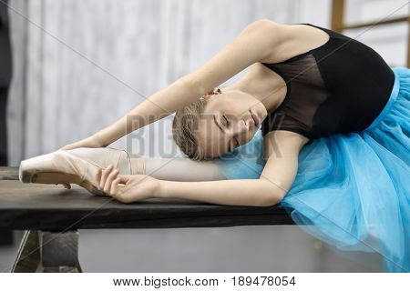 Cute ballerina leans with stretched arms on her leg on the wooden table on the light wall background in the studio. She wears a black leotard with cyan tutu and pointe shoes. Her eyes are closed.