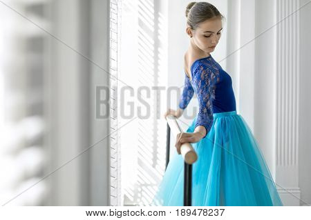 Pretty ballerina with closed eyes stands next to the ballet barre and holds her hands on it on the white wall background. She wears a lace blue leotard with a cyan tutu. Indoors.