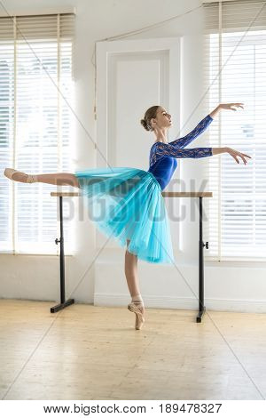 Beautiful ballerina stands on the left toe next to the ballet barre on the white wall and windows background. She wears a lace blue leotard, cyan tutu, pointe shoes and looks forward. Indoors.