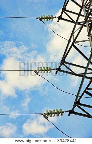 Electrical power insulator taken closeup against of blue cloudy sky.