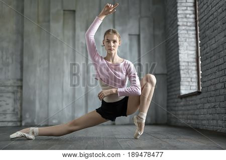 Gorgeous ballerina does half-split next to the window on the gray wall background. Her left leg is on the toe. Girl wears black shorts, light leotard with lilac blouse and pointe shoes. Indoors.