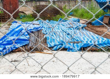 Pile Of Rusty Rebars In Construction Site Through Metal Mesh Fence