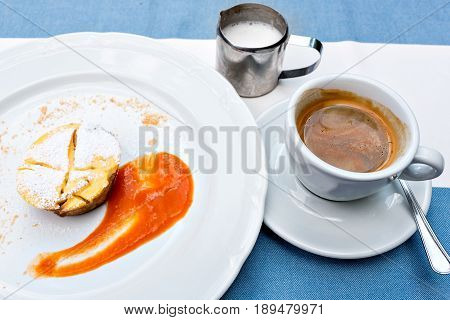 Viennese Apple strudel with fruit sauce on a plate. not a classic shape in a unique way. a Cup of coffee and a warm frothed milk.
