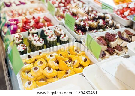 Assorted marinated vegetables and olives on farmer's market in small town in Europe.