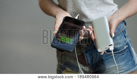 girls hands hold of the phone and charger. Powerbank and smartphone in girl's hands. Energy charger power bank smart phone. Still life modern digital concept.