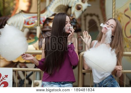 Two young women sharing cotton candyfloss at amusement park. Best friends eating cotton candy together outdoors.