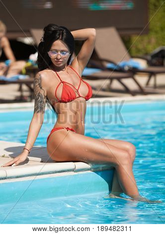 Beautiful sexy young woman with perfect slim figure with long dark hair and wet bathing suit fashion in stylish glasses from the sun is sunning by swimming pool swim, sunbathe have fun at beach party