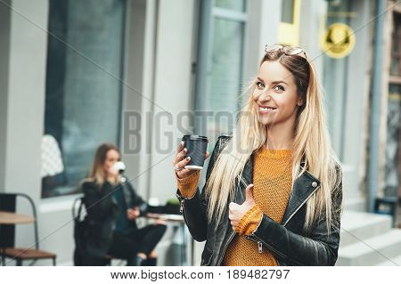 Take away coffee. Beautiful young urban woman wearing in stylish clothes holding coffee cup and smiling while walking along the street. Student's coffee break after study. Fashion lifestyle.