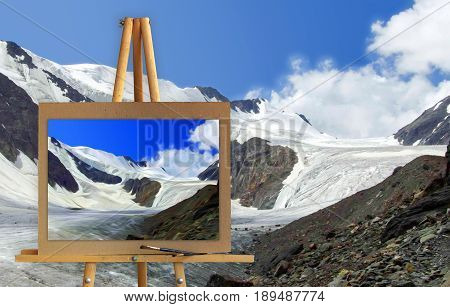 Easel With A Painting Watercolor Landscape Of High Mountains With Peaks Covered By Snow At Winter  P