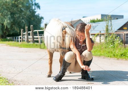 Lets play! Cheerful teenage girl sitting near cute little shetland pony. Multicolored summertime horizontal outdoors image.
