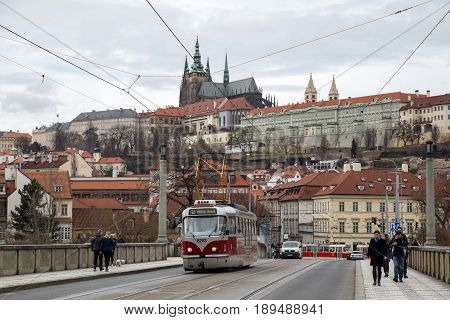 Prague, Czech Republic - March 20, 2017:  A red tram and people on a bridge with Prague Castle in the background