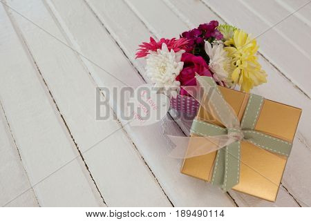 Gift box and bunch of fresh flowers with I love you mom card on wooden surface