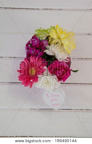 Bunch of fresh flowers with I love you mom card on wooden surface