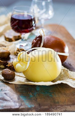 Sicilian sweet dessert liqueur wine Marsala in glass hard cheese Caciocavallo or Provolone dried figs with figs bread still life on wooden table