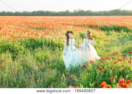 kid fashion, style, friendship, childcare concept - two lovely princesses with wreaths on heads and and trendy sleeveless dresses walking through the field of wild flowers