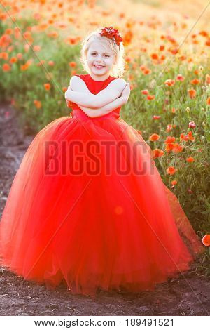 wedding, celebration, birthday, childcare, spring, nature concept - fascinating little princess in rich red dress with short blonde hair hugging herself and laughing surrounded by poppies