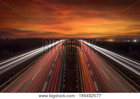 Driving on highway at dusk towards the city lights. Light trails on motorway at beautiful sunset long exposure image.