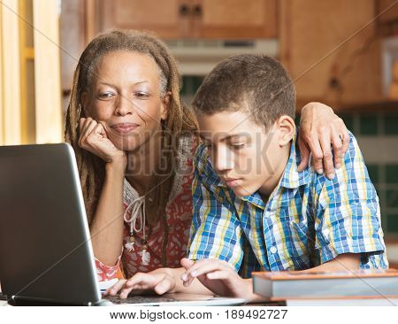 Mother And Teen Son Work In Kitchen On Laptop