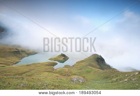 low fog over alpine lake in morning Schrecksee