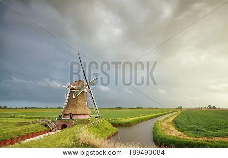 rainy sky over Dutch windmill in Holland