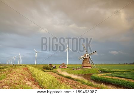 old windmill and turbines at rainy sunset Netherlands