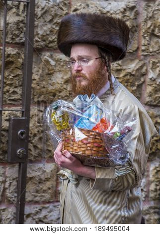 JERUSALEM - MARCH 13 : Ultra Orthodox man holding Mishloach Manot during Purim in Mea Shearim Jerusalem on March 13 2017 Mishloach Manot is traditional food gifts given during Purim